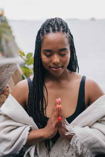 woman with braided hair meditating outdoors
