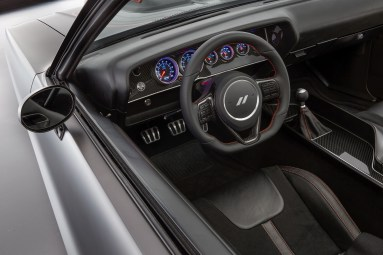 The interior of the Dodge Shakedown Challenger is further transformed with modern modifications including a black leather shift boot capped by an SRT Hellcat gearshift knob and black Mopar instrument panel gauges contrasted with gloss carbon fiber instrument panel cluster trim.