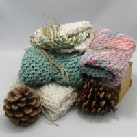 Picture of 4 folded cotton dish cloths stacked with 2 pine cones