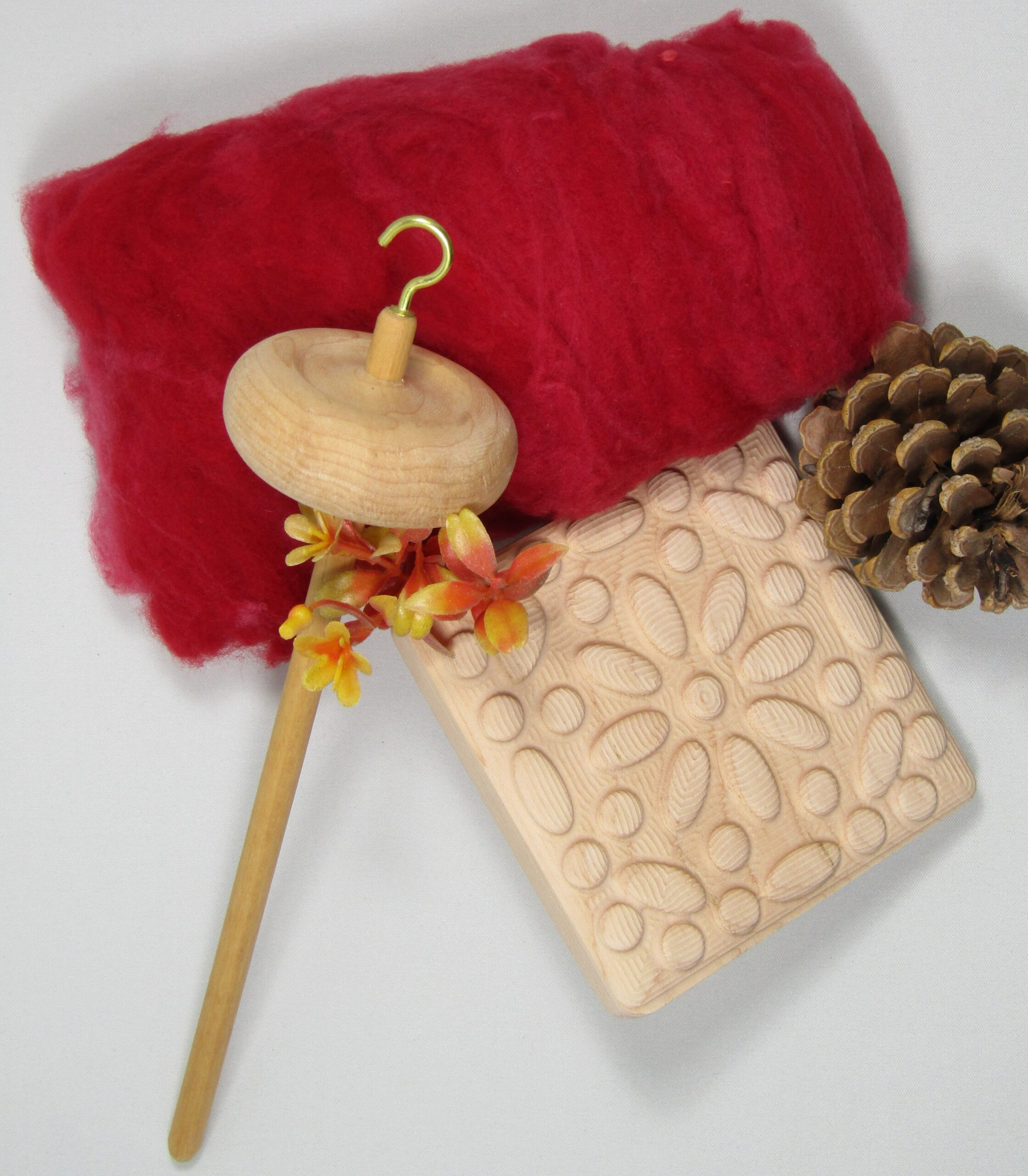 A wood drop spindle, red wool and wood felting tool