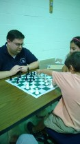 Tobias wants to compete as well. Here he takes a lesson from the 2012 Virginia Chess Champion, Coach Justin.