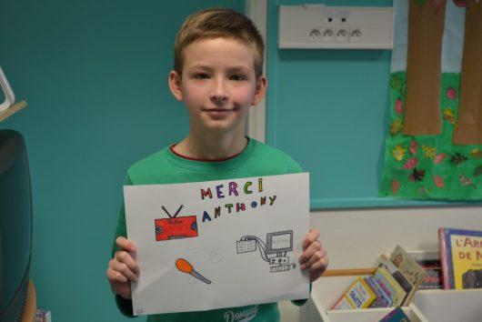"""Nous voyons un élève de CM1 exposer son dessin sur lequel est noté """"Merci Anthony"""""""