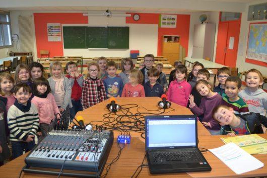 """Les 20 élèves de grandes sections sont installés autour des micros afin de chanter """"Promenons-nous dans les bois"""""""