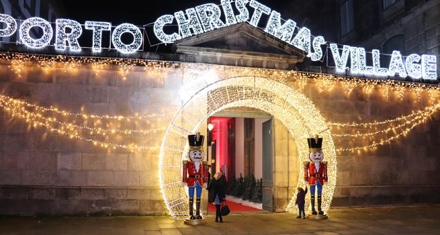 Entrada do Porto Christmas Village com muitas luzes natalinas douradas. Dois soldadinhos de chumbo estão do lado da porta