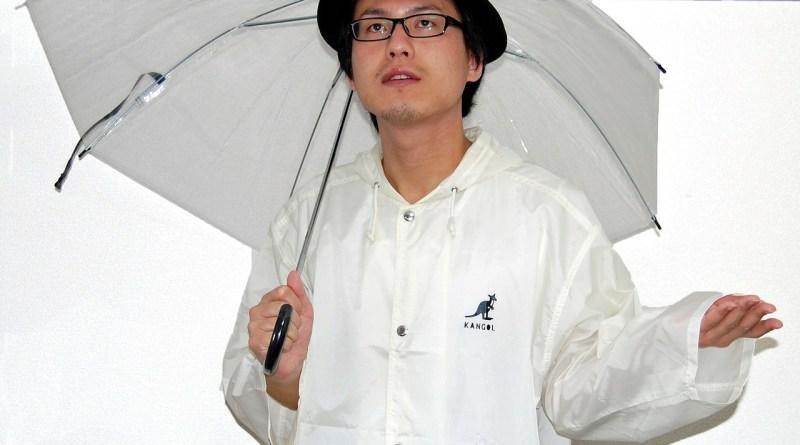 Un homme vêtu d'un imperméable avec un parapluie prêt à affronter la météo