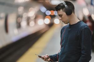 Un jeune homme tient un téléphone cellulaire avec des écouteurs