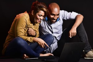 Un couple qui rit en regardant l'écran d'un ordinateur