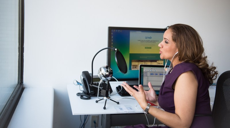 Une femme assise devant un ordinateur et un micro