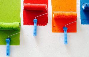 Quatre rouleaux qui appliquent de la peinture sur un mur