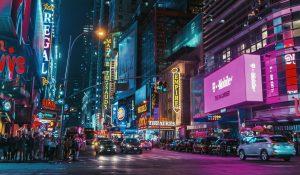 Une ville la nuit avec des panneaux publicitaires de plusieurs grandes entreprises