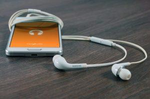 Un smartphone Samsung blanc à côté d'écouteurs sur tableau marron