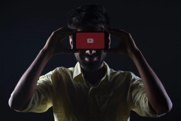 Quelqu'un tenant un téléphone portable avec le logo YouTube à l'écran