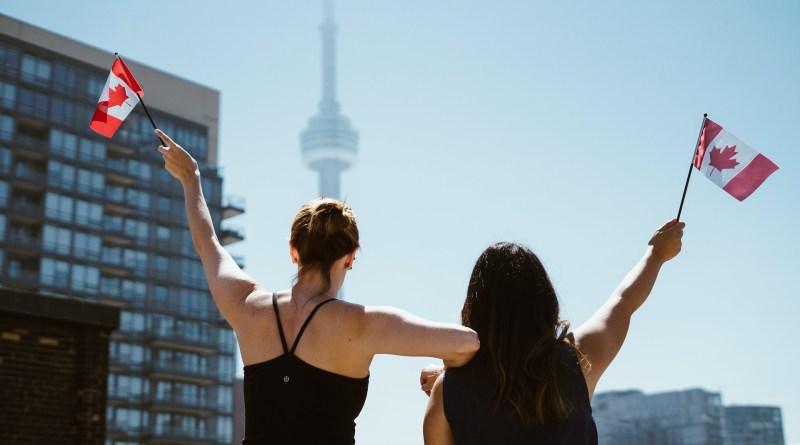 Deux jeunes filles agitent un drapeau canadien
