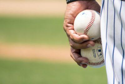 Un lanceur tient deux balles de baseball