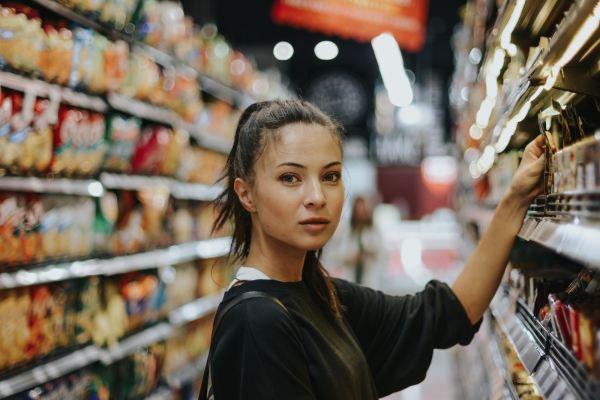Une jeune femme dans les allées d'un supermarché