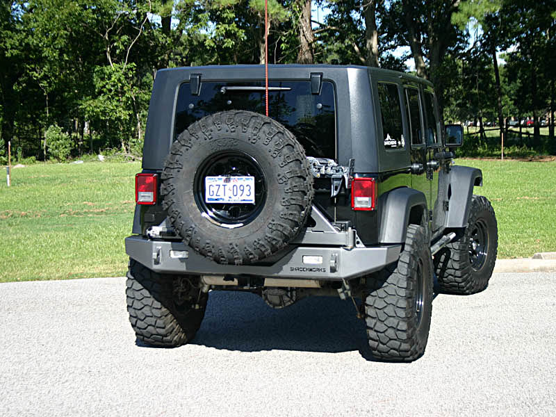 grey jeep in parking with a CB antenna tire rock mount
