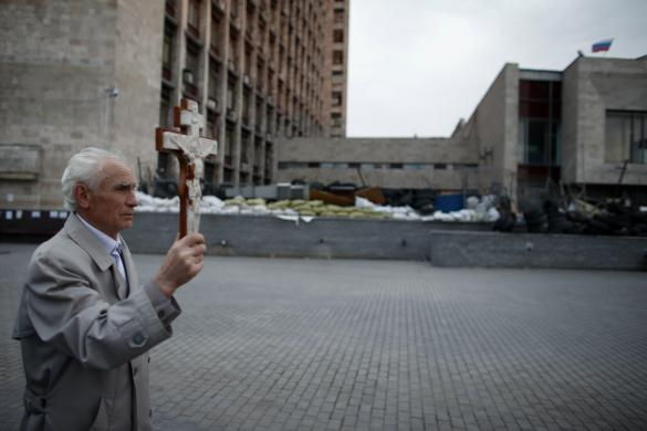A Ukrainian Orthodox Christian walks with a cross outside a regional government building in Donetsk