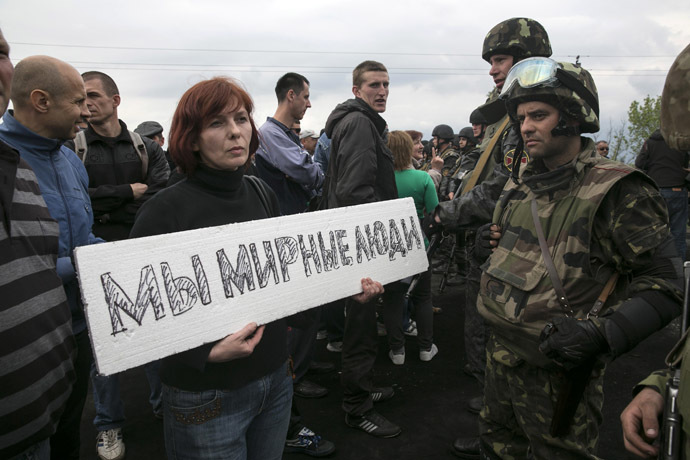 A civilian holds a sign in front of Ukrainian troops at a checkpoint near the town of Slaviansk in eastern Ukraine
