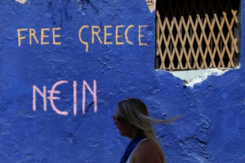 A tourist passes a graffiti in the Plaka tourist district of Athens, Wednesday, July 8, 2015. Greece made a request for aid from Europe's bailout fund Wednesday as it rushed to deliver details of its proposed economic reforms in time to secure the country's future in the euro and avoid a descent into financial chaos. (AP Photo/Thanassis Stavrakis)
