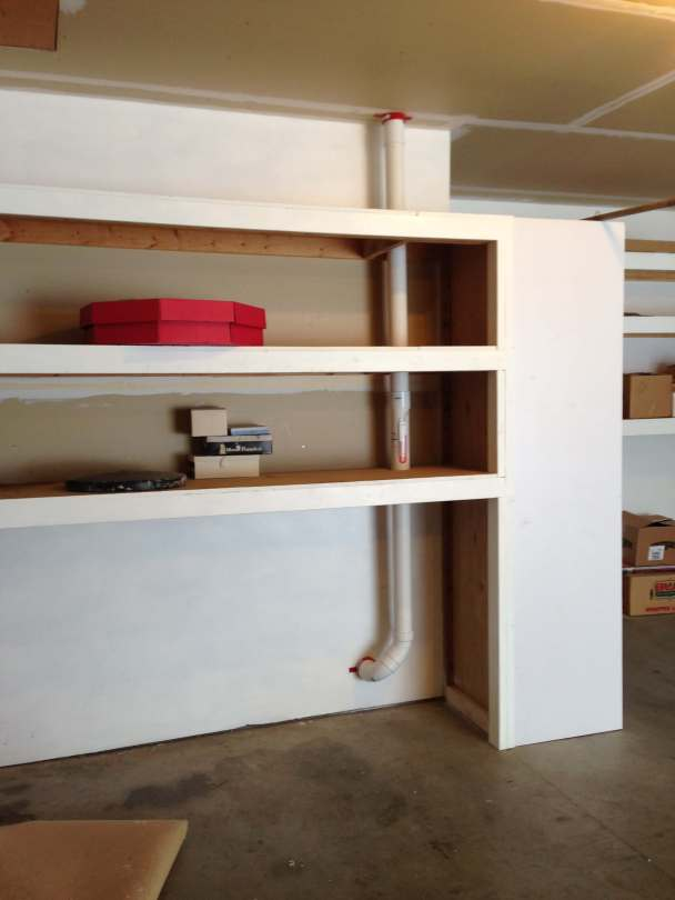 Radon mitigation system pipe going through a garage with a shelving unit.
