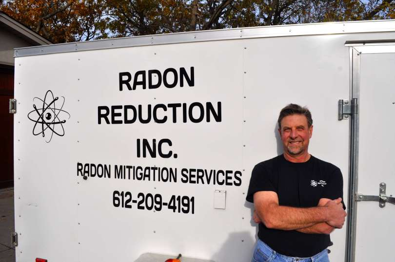 Radon Reduction employee standing in front of a trailer.