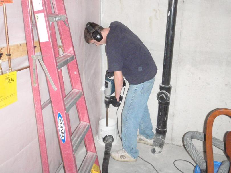 Radon Reduction employee drilling a hole through a basement floor for a radon mitigation system.
