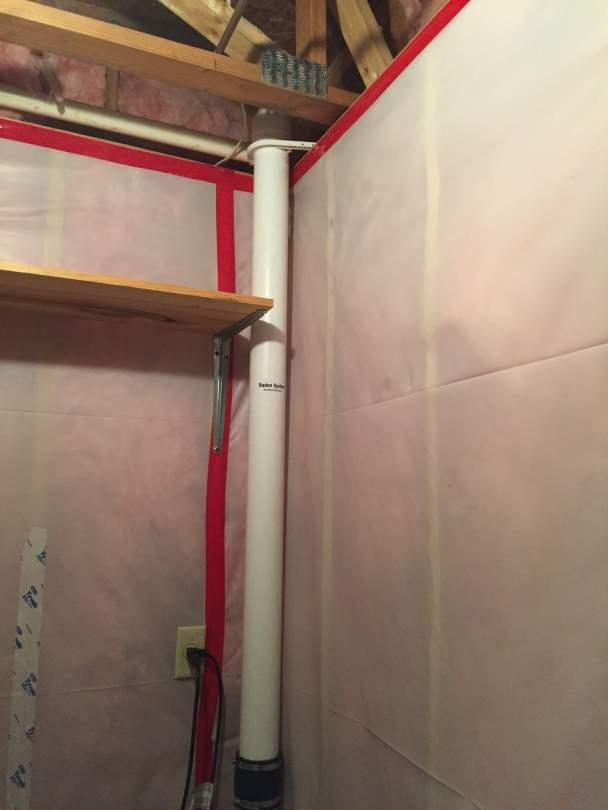 A radon vent pipe in a basement