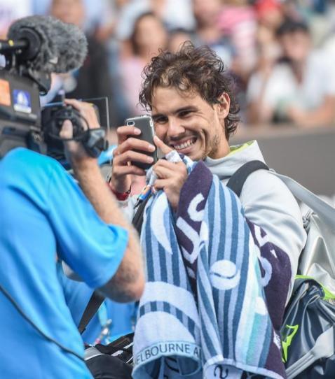 Rafael Nadal takes a photo of his sign on camaera Australian Open 2015