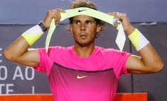 Rafael Nadal of Spain puts on his headband, during a break of his men's singles tennis semi-final match against Fabio Fognini of Italy, at the Rio Open