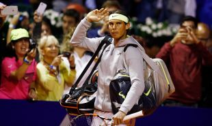 Spain's Nadal waves as fans take pictures as he arrives for his tennis match against Argentina's Arguello at the ATP Argentina Open in Buenos Aires