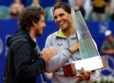 Spain's Rafael Nadal receives the trophy from former Roland Garros champion Gaston Gaudio after winning his final match against Argentina's Juan Monaco at the ATP Argentina Open tennis tournament in Buenos Aires