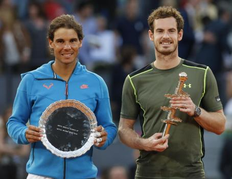 Andy Murray of Britain, right, holds the winners trophy as he poses with runner-up, Rafael Nadal of Spain, after their men's singles final match at the Madrid Open Tennis tournament in Madrid, Spain, Sunday, May 10, 2015. Murray defeated Rafael Nadal 6-3, 6-2. (AP Photo/Paul White) )