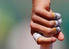 The bandaged fingers of Rafael Nadal of Spain are seen as he holds his racket during the men's singles match against Andrey Kuznetsov of Russia at the French Open tennis tournament at the Roland Garros stadium in Paris, France, May 30, 2015. REUTERS/Gonzalo Fuentes TPX IMAGES OF THE DAY