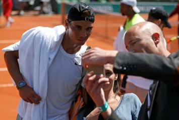 Rafael Nadal of Spain poses for selfies after a training session for the French Open tennis tournament at the Roland Garros stadium in Paris, France, May 22, 2015. REUTERS/Vincent Kessler