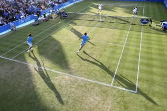 Spain's Marc Lopez and Spain's Rafael Nadal, bottom, play Canada's Daniel Nestor and India's Leander Pes during their doubles tennis match at the Queen's Championships in London, Thursday, June 18, 2015. (AP Photo/Tim Ireland)