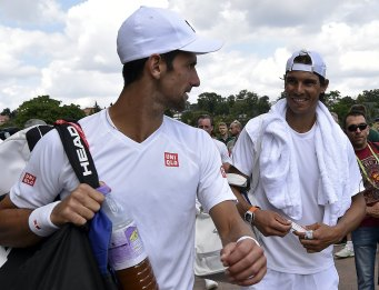Serbia's Novak Djokovic (L) and Spain's Rafael Nadal chat as they leave practice courts at Wimbledon in London June 27, 2015. The Wimbledon tennis championships begins on Monday. REUTERS/Toby Melville
