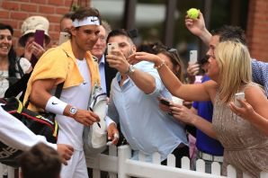 Rafael Nadal poses for photos with fans as he leaves the court for a rain delay during his match with Robin Haase on day four of The Boodles at Stoke Park, near Stoke Poges, England, Friday June 26, 2015. (Mike Egerton/PA via AP) UNITED KINGDOM OUT NO SALES NO ARCHIVE