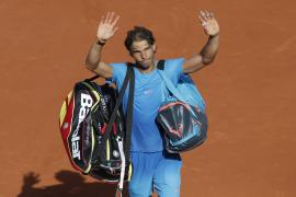 Spain's Rafael Nadal waves goodbye to spectators as he leaves center court while Serbia's Novak Djokovic celebrates winning the quarterfinal match of the French Open tennis tournament in three sets, 7-5, 6-3, 6-1, at the Roland Garros stadium, in Paris, France, Wednesday, June 3, 2015. (AP Photo/Christophe Ena)