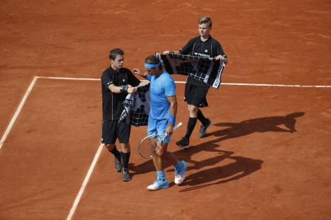 Spain's Rafael Nadal takes a towel from one of the ball-boys in the fourth round match of the French Open tennis tournament against Jack Sock of the U.S. at the Roland Garros stadium, in Paris, France, Monday, June 1, 2015. (AP Photo/Michel Euler)