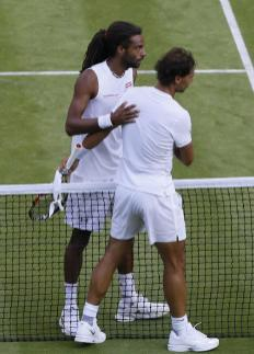 Rafael Nadal of Spain, right, and Dustin Brown of Germany shakes hands at the net after Brown defeated Nadal in their singles match at the All England Lawn Tennis Championships in Wimbledon, London, Thursday July 2, 2015. (AP Photo/Kirsty Wigglesworth)