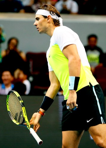 Spain's Rafael Nadal of the Indian Aces plays with his racket during his men's singles match against Czech Republic's Tomas Berdych of the UAE Royals in the International Premier Tennis League Monday, Dec. 7, 2015 at the Mall of Asia Arena in Pasay city, south of Manila, Philippines. Nadal won 6-5. (AP Photo/Bullit Marquez)