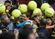 Spain's Rafael Nadal of the Indian Aces is mobbed by his Filipino fans following his win over the Czech Republic's Tomas Berdych of the UAE Royals in the men's singles of the 2015 International Premier Tennis League Monday, Dec. 7, 2015 at the Mall of Asia Arena in suburban Pasay city, south of Manila, Philippines. (AP Photo/Bullit Marquez)