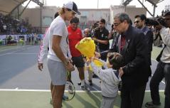 Spain's Rafael Nadal is presented with a bouquet by a child at a promotional event in New Delhi, India, Thursday, Dec. 10, 2015. Nadal, who plays for Indian Aces in the International Professional Tennis League (IPTL), is in India to play a leg of the league. (AP Photo/Altaf Qadri)
