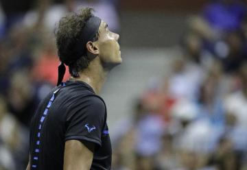 Rafael Nadal, of Spain, looks up at light rain during a match against Andreas Seppi, of Italy, during the U.S. Open tennis tournament, Wednesday, Aug. 31, 2016, in New York. (AP Photo/Julio Cortez)
