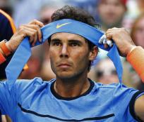 Rafael Nadal, of Spain, puts on a clean headband during his match with Lucas Pouille, of France, during the fourth round of the U.S. Open tennis tournament, Sunday, Sept. 4, 2016, in New York. (AP Photo/Alex Brandon)