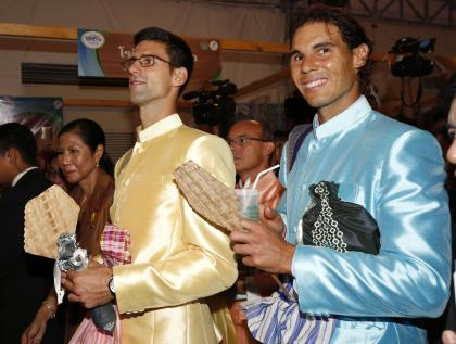 Tennis players Rafael Nadal, right, of Spain and Novak Djokovic, left. of Serbia visit a fair after meeting with Thai Prime Minister Prayuth Chan-ocha outside Government House in Bangkok, Thailand Friday, Oct. 2, 2015. Djokovic will face Nadal in the tennis exhibition match in Bangkok to boost confidence in Thailand's safety after a deadly Aug. 17 bombing that left 20 dead in the heart of the capital. (Rungroj Yongrit/Pool Photo via AP)