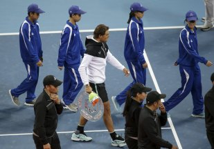 Runner-up Rafa Nadal of Spain walks off the court with staff members with his trophy during the award ceremony after the men's singles final match against Novak Djokovic of Serbia at the China Open Tennis Tournament in Beijing, China, October 11, 2015. REUTERS/Jason Lee