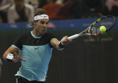 Rafael Nadal of Spain returns a shot against Novak Djokovic of Serbia, during exhibition tennis match in Bangkok, Thailand, Friday, Oct. 2, 2015.Djokovic beat Nadal 6-4, 6-2. (AP Photo/Sakchai Lalit)