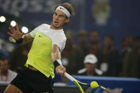 Rafael Nadal of Indian Aces returns a shot against Roger Federer of UAE Royals in the men's singles event of the International Premier Tennis League in New Delhi, India, Saturday, Dec. 12, 2015. (AP Photo/Tsering Topgyal)