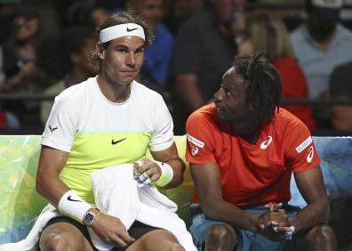 Rafael Nadal of Spain, left, chats with Gael Monfils of France, on the bench during a break as Nadal plays Lleyton Hewitt of Australia at the Fast4 tennis tournament in Sydney, Australia, Monday, Jan. 11, 2016.(AP Photo/Rob Griffith)